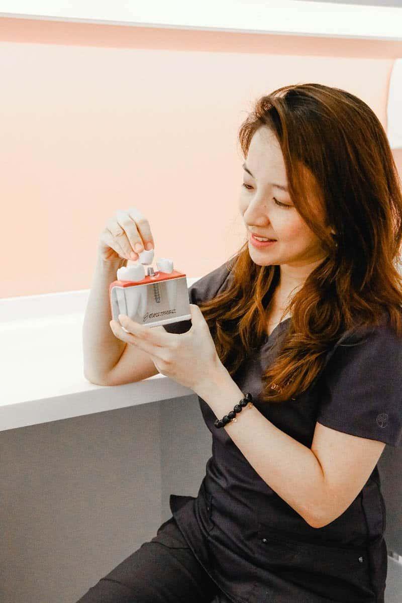 Dr Marlene Teo holding dental implant model