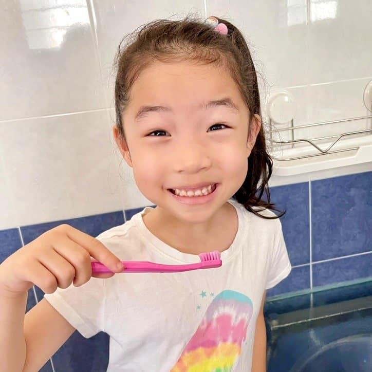 Little girl using toothbrush